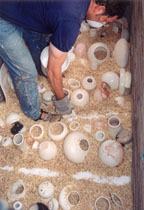 Pit Firing: Loading pots into the pit.