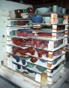 After the firing and he kiln has cooled, the kiln is opened and the copper red pots are now visible.
